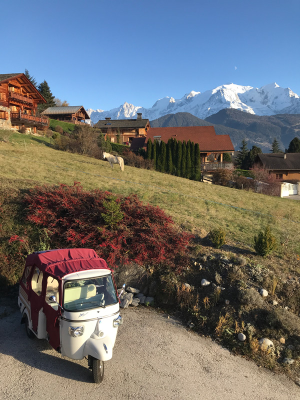 Piaggio APE Calessino carrosserie blanche et capote rouge grenat sur fond du massif du Mont Blanc.