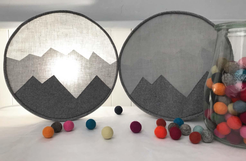 Applique ronde silhouette de montagnes visibles à l'horizon. Camaïeu de gris, drap de laine et lin.