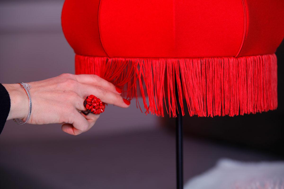 abat jour art déco drap de laine et frange rouge. Main joue avec la frange