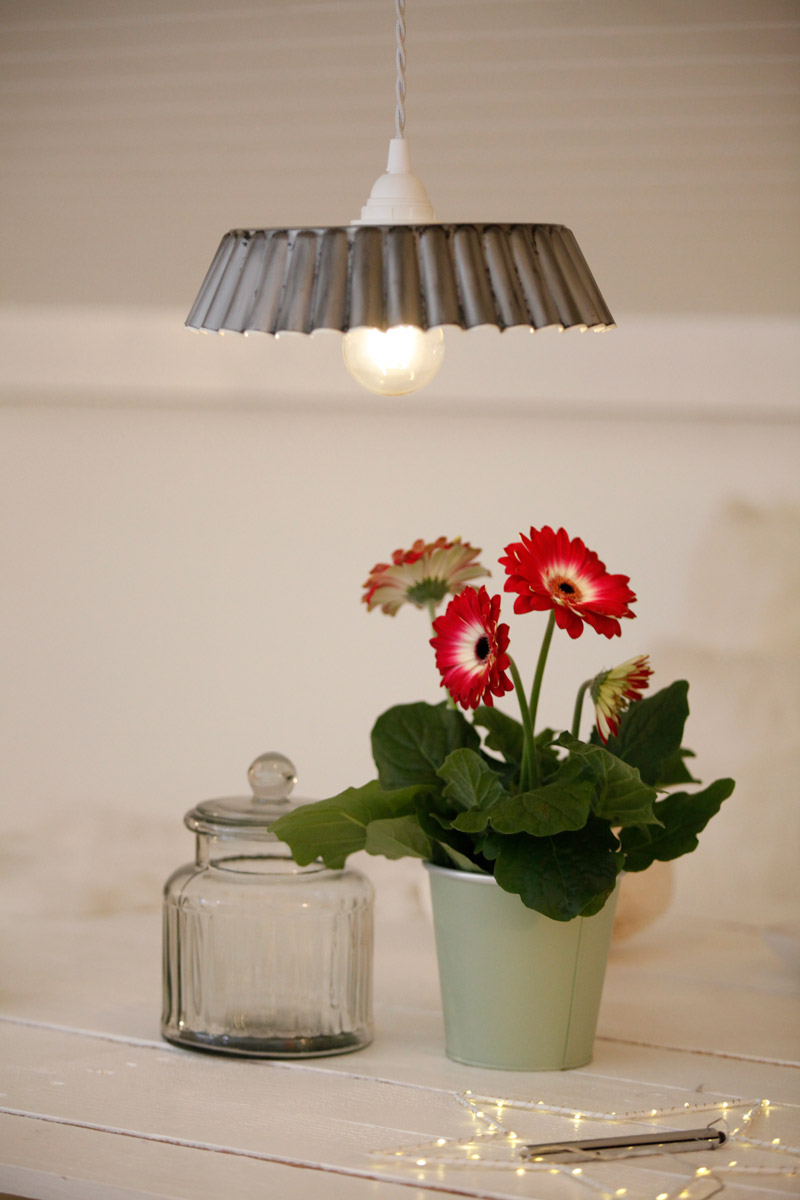 abat jour suspension éclairée réalisée avec un moule à gâteau ancien au dessus d'un pot de Gerberas roses et blancs